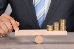 Businessman balancing coins on wooden seesaw Royalty Free Stock Photos