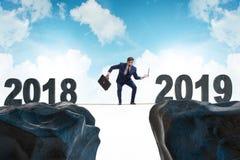 The businessman balancing between 2018 and 2018 stock photo
