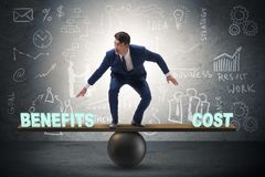 Businessman balancing between cost and benefit in business conce. Pt Royalty Free Stock Photography