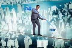 The businessman balancing between debt and tax Stock Images