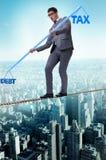 The businessman balancing between debt and tax Stock Photos