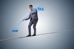 The businessman balancing between debt and tax Royalty Free Stock Images