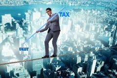 The businessman balancing between debt and tax Stock Photo