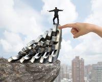 Businessman balancing falling Euro symbols with woman hand helpi Royalty Free Stock Photos