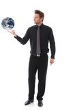 Businessman balancing globe on forefinger Stock Photos