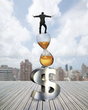 Businessman balancing on hourglass and dollar sign Stock Image