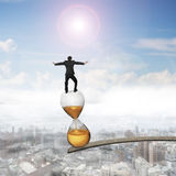 Businessman balancing hourglass on edge of wooden plank Royalty Free Stock Photo