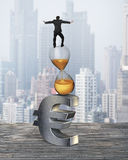 Businessman balancing on hourglass and euro sign Stock Photography