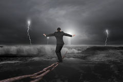 Businessman balancing on old iron chain with dark stormy ocean Stock Photo