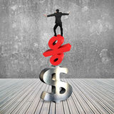 Businessman balancing on red percent symbol and dollar sign stock image