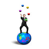 Businessman balancing on sphere juggling with balls Stock Images