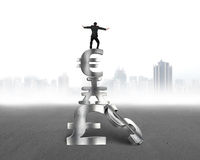 Businessman balancing on stack money symbols Stock Image