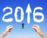 Businessman balancing tightrope woman hands holding 2016 arrow c Stock Photos