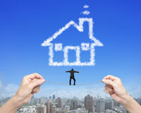 Businessman balancing tightrope woman hands holding house shape Royalty Free Stock Photography