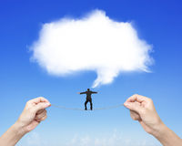 Businessman balancing tightrope woman hands holding white cloud. Businessman balancing on tightrope woman two hands holding, with white cloud thought bubble in Stock Photography