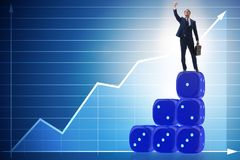 Businessman balancing on top of dice stack in uncertainty concep. T Stock Photography