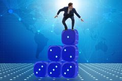Businessman balancing on top of dice stack in uncertainty concep. T Royalty Free Stock Images