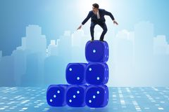 Businessman balancing on top of dice stack in uncertainty concep. T Royalty Free Stock Image