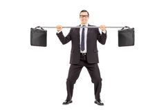 Businessman balancing two briefcases on a pipe Stock Photography