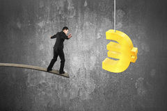 Businessman balancing on wooden board with golden euro symbol Royalty Free Stock Photography