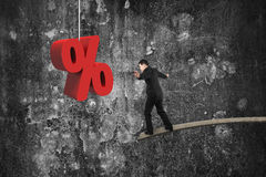 Businessman balancing on wooden board with red percentage sign Stock Photos