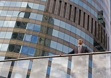 Businessman on the balcony. Businessman on skyscraper balcony  surveying the opportunities Stock Images