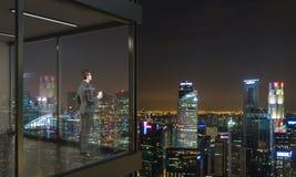 Businessman on balcony at night Royalty Free Stock Photo