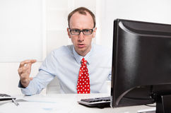 Businessman with bald and glasses aggressive and in rage sitting Stock Photo