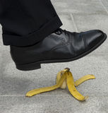 Man stepping on banana peel, skin in street, work accident, danger. Businessman about to step on a banana skin Stock Image
