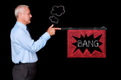 Businessman BANG. Photo of a mature businessman against a black background firing a chalk drawn gun with a BANG flag. Gun was drawn on a blackboard then royalty free stock photo