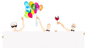 Businessman with banner, balloons and wine. Wooden Dummy businessman with banner, balloons and wine making toast  Isolated Stock Image