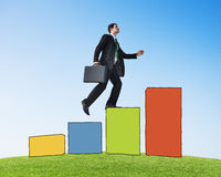 Businessman on a Bar Graph Moving Up Stock Photography