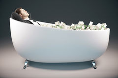 Businessman in bathtub with cash. Handsome relaxing businessman lying in bathtub filled with dollar banknotes on grey background. Success concept. 3D Rendering Royalty Free Stock Photography