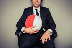 Businessman with beach ball in office chair Stock Photos