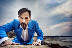 Businessman on the beach, day,outdoor. Businessman makes his way through obstacles. Middle-aged man in blue costume and white shirt. Success business concept Stock Image