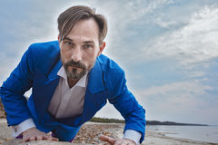 Businessman on the beach, day,outdoor. Businessman makes his way through obstacles. Middle-aged man in blue costume and white shirt. Success business concept Royalty Free Stock Photo