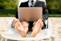 Businessman on the beach. Businessman dressed in suit and shorts working with laptop on the sunbed at the beach Royalty Free Stock Photos