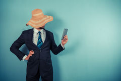 Businessman with beach hat reading on tablet Stock Photo