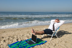 Businessman on beach with laptop Royalty Free Stock Photo