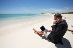 Businessman on the beach working with computer and speaking on phone Stock Photos