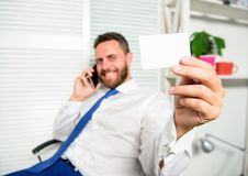 Businessman bearded guy sit office feel confident. Man hold business or bank card copy space. Here is my number. Feel royalty free stock photography