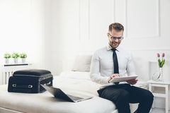 Businessman on bed working with a tablet and laptop from his hotel room Royalty Free Stock Photography