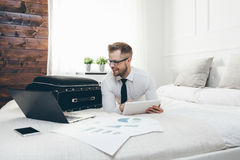 Businessman on bed working with a tablet and laptop from his hotel room Royalty Free Stock Images