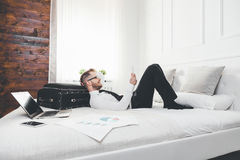 Businessman on bed working with a tablet and laptop from his hotel room Royalty Free Stock Photo