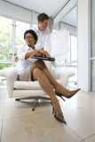 Businessman behind businesswoman with laptop computer in armchair, portrait, low angle view Stock Photo