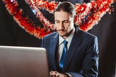 Businessman behind a laptop in the new year stock image