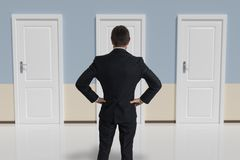 Businessman from behind is making decision and selecting the door.  Royalty Free Stock Photo
