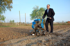 The businessman behind a tractor. To the young man most to have to plough a field royalty free stock photography