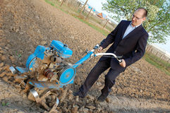 The businessman behind a tractor. Royalty Free Stock Photo