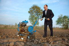 The businessman behind a tractor. To the young man most to have to plough a field stock photography